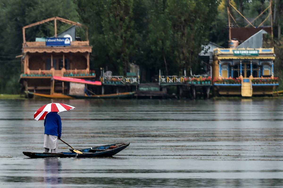 A man stands on a boat under the rain during a lockdown in Srinagar