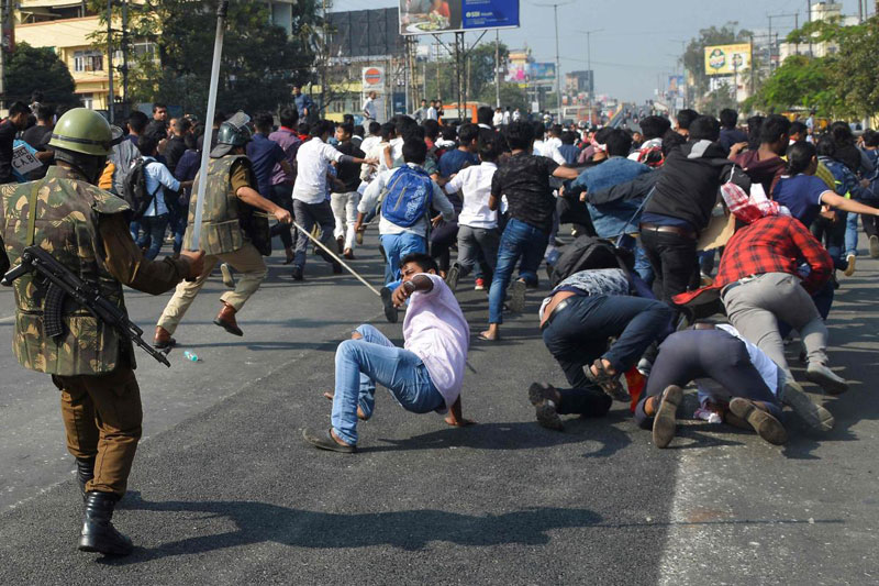 Security personnel use batons to disperse students protesting against the governments Citizenship Amendment Bill (CAB), in Guwahati