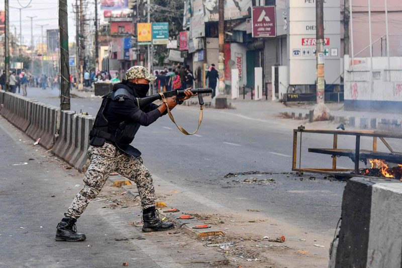 A security personnel fires tear gas during a curfew in Guwahati on December 12, 2019,