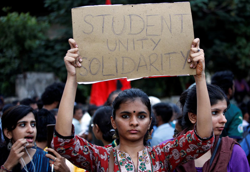 demonstrator displays a placard during a protest march to show solidarity with the students of New Delhi's Jamia Millia Islamia university