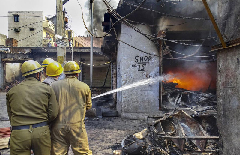 Firefighters attempt to douse fire in a burning shop following clashes over the new citizenship law, in Gokulpuri area of northeast Delhi
