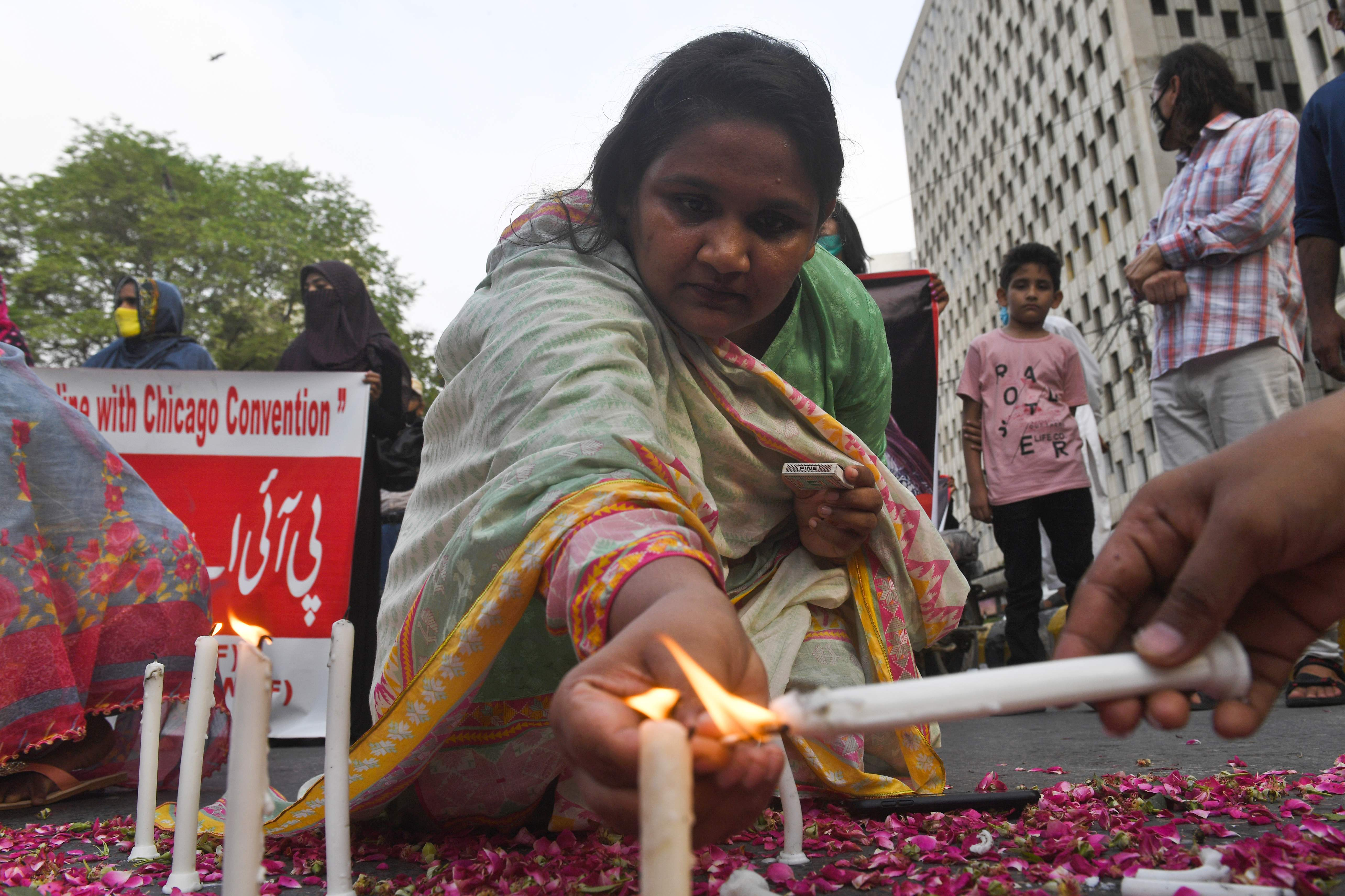Trade union and civil society activists light candles in Karachi on May 28, 2020, during a candlelight vigil for the victims of the Pakistan International Airlines (PIA) plane crash on May 22. (AFP Photo)