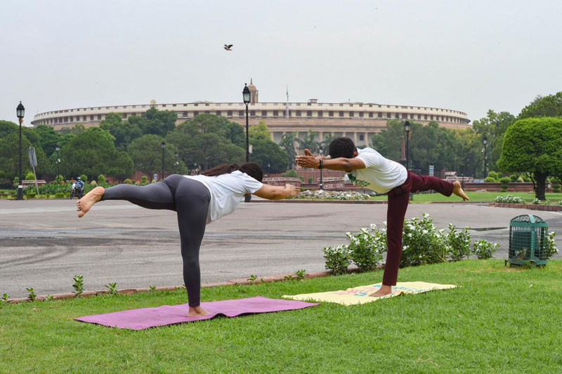 Youngsters perform 'yoga' at a lawn near Vijay Chowk on the 6th International Day of Yoga, in New Delhi,