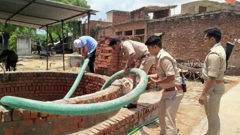 Police personnel pump water out of a well at gangster Vikas Dubey's residence in Kanpur to see if weapons were hidden in it
