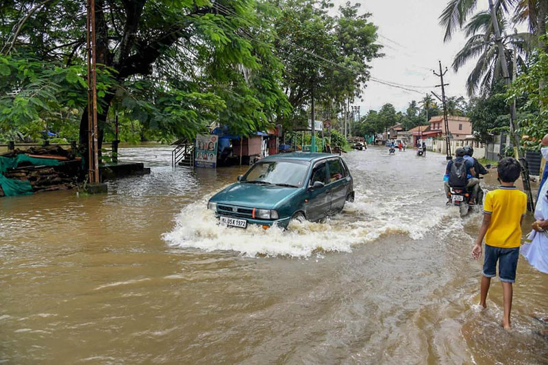 A vehicle moves slowly through a waterlogged street following heavy rainfall, in Kottayam district