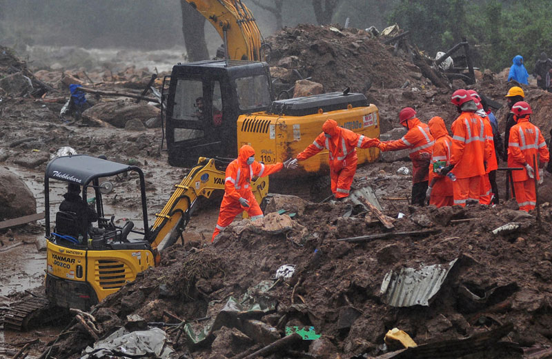 Rescue workers look for survivors at the site of a landslide during heavy rains in Idukki