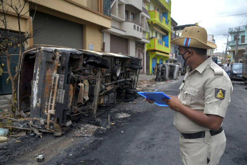 A policeman takes notes next to burnt police vehicles in Bangalore on August 12, 2020