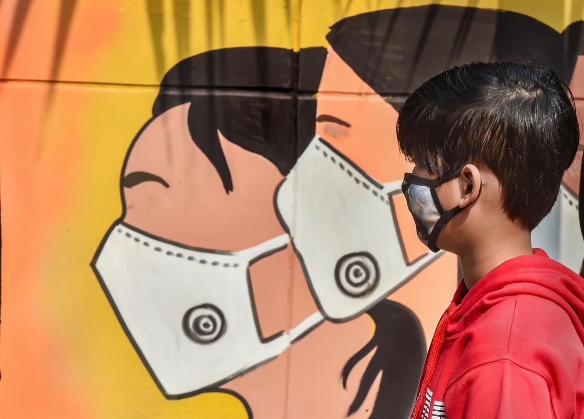A boy wearing face mask walks past a mural on novel coronavirus and protective measures, in New Delhi. Credit: PTI