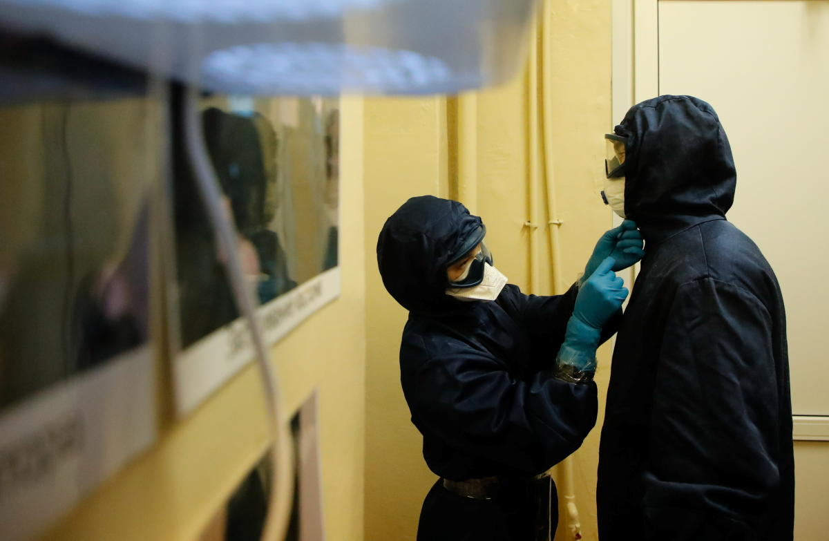A medical specialist is helped by a colleague to put on personal protective equipment (PPE) at the Vologda City Hospital Number 1, where patients suffering from the coronavirus disease (COVID-19) are treated, in Vologda, Russia November 24, 2020. REUTERS/Anton Vaganov