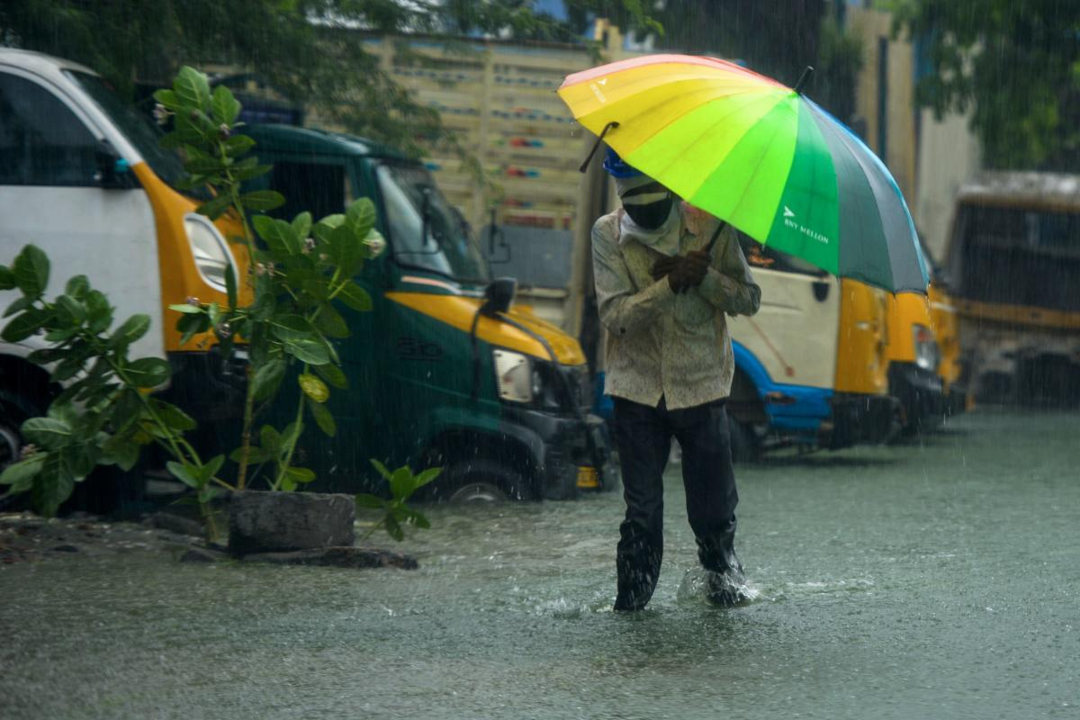 A man walks along a flooded street under heavy rains in Chennai as cyclone Nivar approaches the southeastern coast of the country on November 25, 2020.