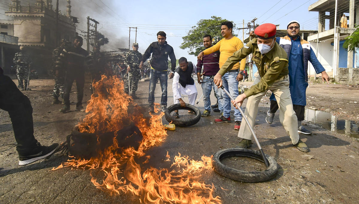 Nagaon: A policeman attempts to douse a burning tyre, set ablaze by demonstrators in support of the nationwide strike, called by agitating farmers to press for repeal of the Centre's agri laws, in Nagaon, Tuesday, Dec. 8, 2020. (PTI Photo)