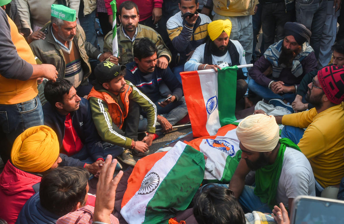 Farmers sit near the mortal remains of a protestor, who died after his tractor overturned during 'Kisan Gantantra Parade' to protest against Centre's farm reform laws, on the occasion of 72nd Republic Day, at ITO in New Delhi, Tuesday, Jan. 26, 2021. (PTI Photo/Shahbaz Khan)