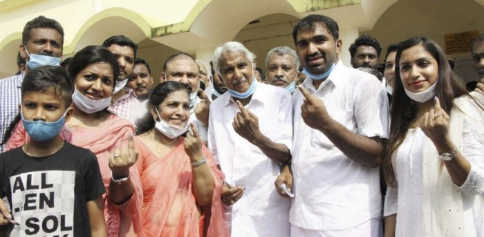 Congress leader Oommen Chandy (C) with his family members after casting their votes in Kerala. Credit: PTI Photo