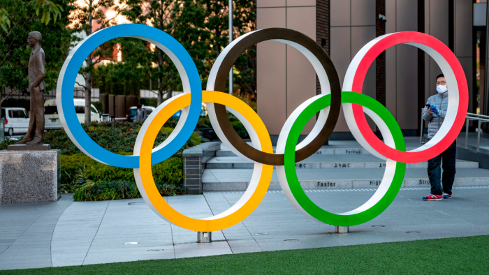This picture taken on January 20, 2021 shows a visitor taking photos of the Olympic rings outside the Olympic Museum in Tokyo. Credit: AFP File Photo